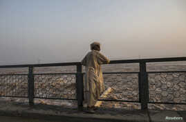FILE - A man watches as water is discharged at a dam in Jhang, Pakistan, Sept. 10, 2014. Ground was broken Friday on an $81 million U.S.-funded component of a dam project in Pakistan's volatile tribal area of North Waziristan.