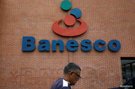 A man walks past the corporate logo of Banesco bank at one of its branches in Caracas, Venezuela, May 3, 2018.