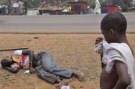 A child looks at a man  suspected of suffering from the Ebola virus, while holding his hand over his nose,  in a main street and busy part in Monrovia, Liberia, Friday, Sept. 12, 2014. A Western Kentucky University student has developed a way to trac