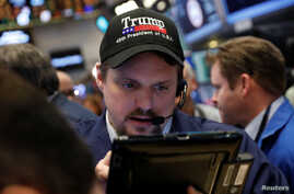 A trader wears a Donald Trump hat while working on the floor of the New York Stock Exchange shortly after the opening bell in New York, March 16, 2017.