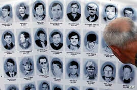 A man looks at a banner with pictures of Serbs killed by Bosnian forces during the 1992-95 Bosnian war in the Srebrenica area, in downtown Belgrade, Serbia, July 10, 2017.