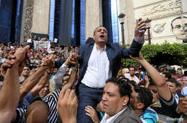 FILE - Journalists carry Yehia Kalash, head of the Egyptian press syndicate, during a protest against restrictions on the press and to demand the release of detained journalists, in front of the Press Syndicate in Cairo, Egypt May 4, 2016.