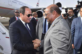In this photo released by the Egyptian Presidency, Egyptian President Abdel-Fattah el-Sissi, left, is greeted by Sudanese President Omar al-Bashir on his arrival to  Khartoum, Sudan, Thursday, July 19, 2018.