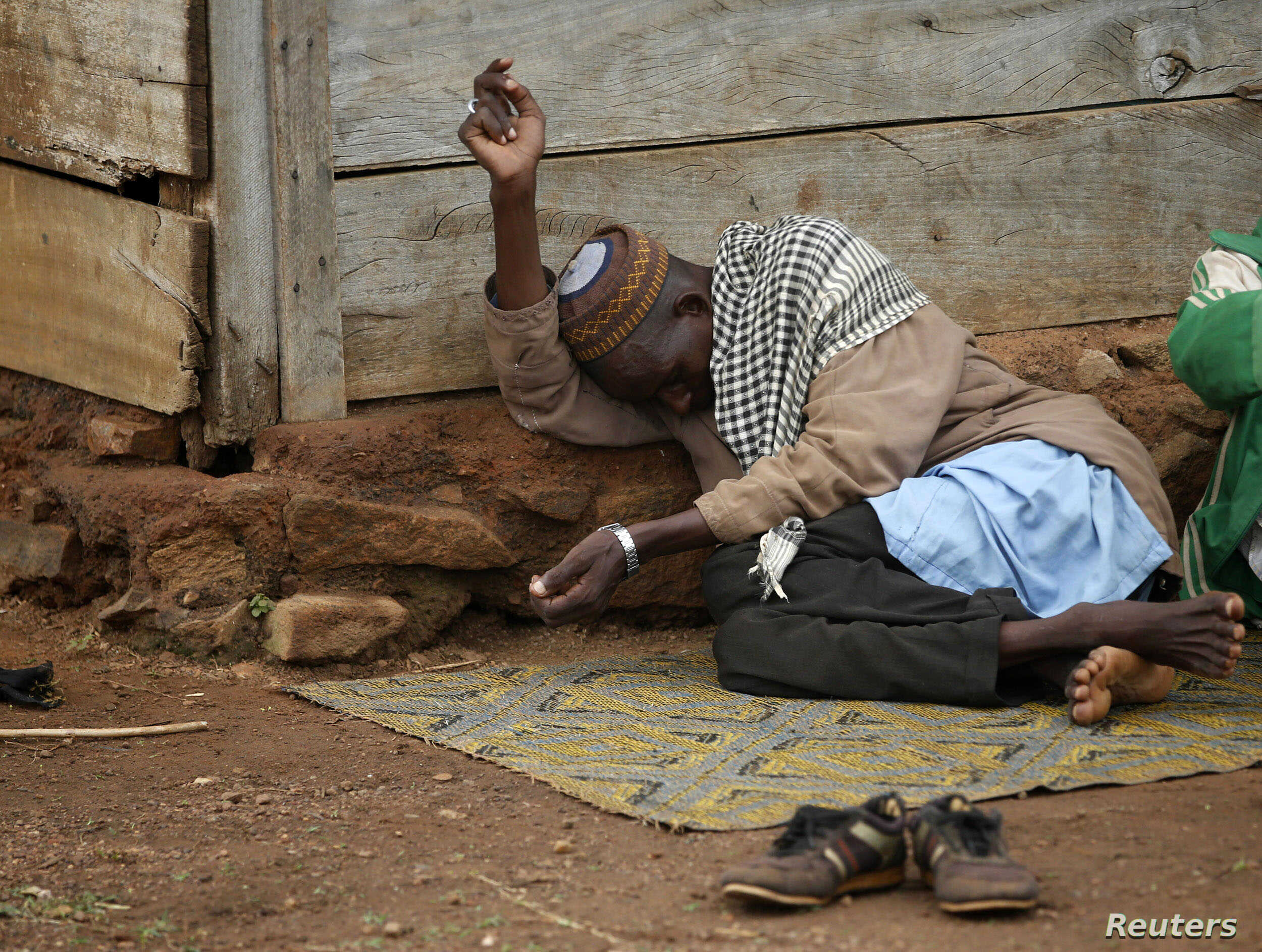 An internally displaced Muslim man lies in front of a house in the town of Boda, Central African Republic, April 15, 2014.