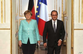 France's President Francois Hollande, right, and German chancellor Angela Merkel arrive to give a press conference, at the Elysee Palace, in Paris, July 6, 2015.