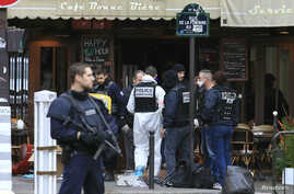 Police investigators work at the scene of a shooting in a bar in Rue de le Fontaine the morning after a series of deadly attacks in Paris , Nov. 14, 2015.