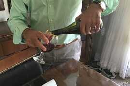 """""""Nabaz"""" pours a glass of his homemade wine """"21 Rays,"""" produced in Iraqi Kurdistan. (S. Behn/VOA)"""