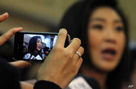 A woman uses her mobile phone to take a picture of Prime Minister-elect Yingluck Shinawatra as she addresses reporters at her party's headquarters in Bangkok, July 13, 2011.