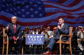 Republican presidential candidate Donald Trump gives a thumbs up as he speaks with retired Lt. Gen. Michael Flynn during a town hall  in Virginia Beach, Va., Sept. 6, 2016.