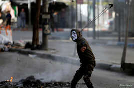 Palestinian protester uses a sling to hurl stones at Israeli troops during clashes in the West Bank city of Hebron Feb. 2, 2018.