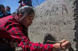 FILE -Catarina Gomez Alonzo writes into the cement of her brother's tombstone after his burial at the cemetery in Yalambojoch, Guatemala, Jan. 27, 2019.