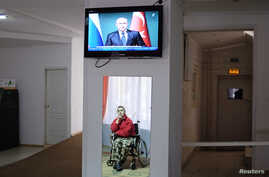 A man in a wheelchair is reflected in a mirror, as he watches a news broadcast showing Russia's President Vladimir Putin speaking at a news conference during his visit to Turkey, at a gerontological centre in Stavropol, southern Russia, Dec. 2, 2014.