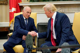 U.S. President Donald Trump shakes hands with John Kelly after he was sworn in as White House Chief of Staff in the Oval Office of the White House in Washington, July 31, 2017.
