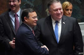 FILE - U.S. Secretary of State Mike Pompeo, left, shakes hands with the foreign minister of Peru Nestor Popolizio Bardales at the United Nations Security Council during a meeting on North Korea, at the United Nations in New York, Sept. 27, 2018.