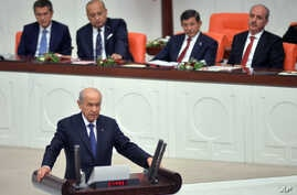 Prime Minister Ahmet Davutoglu (2nd R) and his ministers listen as lawmakers are sworn into office during a ceremony in Ankara, Turkey, June 23, 2015, in an early step in what could be a drawn-out coalition-building process.