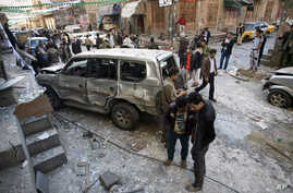 Shiite Houthi men stand near a car damaged by a bomb explosion outside their house in Sanaa Yemen, Tuesday, Dec. 23, 2014.