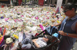 A woman pushes a pram past a temporary memorial site close to the Lindt cafe in the central business district of Sydney, Australia, where people continue to stream past to leave floral tributes Thursday, Dec. 18, 2014.