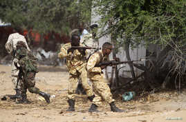Somali government soldiers open fire during an ambush by al-Shabab rebels on the outskirts of Elasha town, Somalia, May 29, 2012.