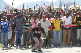Miners sing and dance as they march to Lonmin Platinum Mine near Rustenburg, South Africa, Monday, Sept. 10, 2012, in an attempt to stop operations.
