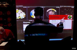 FILE - An analyst points to a screen at Government Communications Headquarters (GCHQ), Britain's electronic intelligence service, in London, March, 14, 2014.