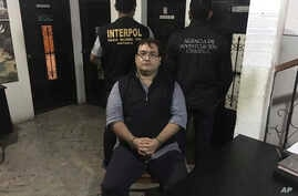 In this photo released by the Guatemala National Civil Police (PNC), Mexico's former Veracruz state Gov. Javier Duarte poses for photos escorted by an agent of the Interpol office in Guatemala (left) and a Mexico federal agent at a court room in Pana