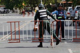 A riot police officer, left, enters a blocked street near the Supreme Court where former party leader Kem Sokha is to appear, in Phnom Penh, Cambodia, Aug. 22, 2018.