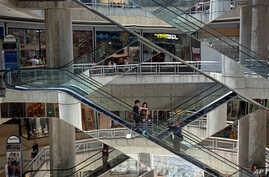 FILE - People ride the nearly empty escalators inside the Sambil mall in Caracas, Venezuela.