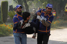 Rescue workers assist an injured student from the shooting at Directorate of Agriculture Institute in Peshawar, Pakistan, Dec. 1, 2017.