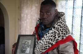 "Chief Zanomthetho Mtirara poses with his leopard skin and a young picture of his adoptive ""grandfather"" Nelson Mandela, who was taken in by the Thembu royal family at the age of 9 when his father died. A leopard skin like this one will be draped over..."