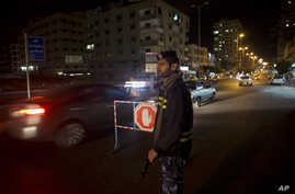 FILE - A Palestinian Hamas police officer monitors the road as a checkpoint is set up at night in Gaza City, May 5, 2015.