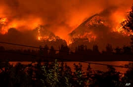 FILE - The Eagle Creek Fire, as seen from near Stevenson Wash., across the Columbia River, burns in the Columbia River Gorge above Cascade Locks, Ore., Sept. 4, 2017.