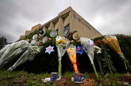 A makeshift memorial of flowers rests on bushes outside the Tree of Life synagogue in Pittsburgh, Nov. 20, 2018. On the quintessentially American holiday of Thanksgiving, some will abandon traditions or choose not to mark the holiday at all. Others w