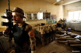 A member of the Iraqi counterterrorism forces stands by an Islamic State militants weapons factory in Falluja, Iraq, June 23, 2016.