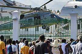 Crowd views US military helicopter landing on grounds of Haiti's presidential palace, 19 Jan 2010