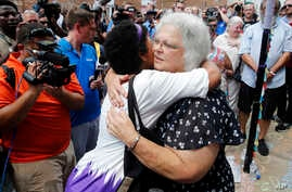 Susan Bro, mother of Heather Heyer who was killed during last year's Unite the Right rally, embraces supporters after laying flowers at the spot her daughter was killed in Charlottesville, Va., Sunday, Aug. 12, 2018.