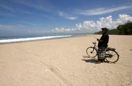 """FILE - A Balinese traditional security guard called """"pecalang"""" patrols the empty Kuta beach, a famous tourist spot on the island, during """"Nyepi"""" or the Day of Silence in Bali, March 16, 2010."""
