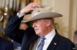 """President Donald Trump tries on a Stetson hat during a """"Made in America,"""" product showcase featuring items created in each of the U.S. 50 states, at the White House, July 17, 2017."""