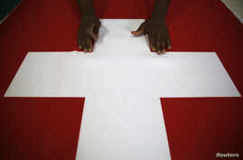 FILE - A worker displays a Swiss flag at the Fabrica de Bandeiras flag factory in Rio de Janeiro, May 29, 2014.