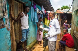 A health worker volunteer talks with a resident on how to prevent and identify the Ebola virus in others, and distributes bars of soap in Freetown, Sierra Leone, Sept. 20, 2014.