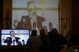 Hamas leaders and supporters listen to Khaled Mashaal, the outgoing Hamas leader in exile, during his news conference in Doha, Qatar, while displayed on a screen at Commodore hotel in Gaza City, Monday, May 1, 2017.