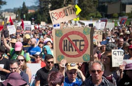 People hold up signs during a rally against hate in Berkeley, California, Sunday, Aug. 27, 2017.