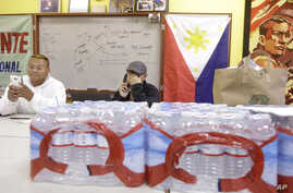 Terrence Valen, president of the National Alliance for Filipino Concerns, center, talks on the phone next to Joey Elacion as they sit behind bottles of water donated by Elacion for victims of Typhoon Haiyan, at the Filipino Community Center in San Fr