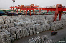 """FILE - Workers ride through an aluminum ingots depot in Wuxi, Jiangsu province, China, Sept. 26, 2012. On Friday, China warned of a """"huge impact"""" on trade if the U.S. places tariffs on steel and aluminum."""