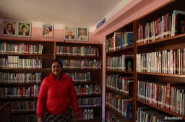 Meera Marahattha stands surrounded by books in the Tribeni community library in Bhimdhunga, Nepal, Feb. 9, 2018.