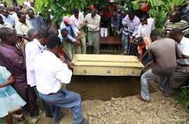 FILE - Pallbearers bury a coffin containing the remains of Francis Kamande, who was killed when unidentified gunmen attacked the coastal Kenyan town of Mpeketoni, June 18, 2014.