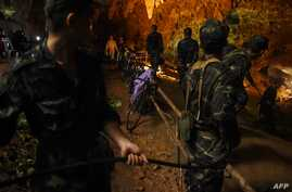 Thai soldiers relay electric cable deep into the Tham Luang cave at the Khun Nam Nang Non Forest Park in Chiang Rai on June 26, 2018 during a rescue operation for a missing children's football team and their coach.