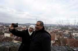 In this photo taken Dec. 16, 2016, Abd Alwahab Alahamad and his wife Iman Mshanati take a selfie atop the castle overlooking the town of Gray, eastern France.