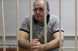 Oyub Titiev, the head of a Chechnya branch of the respected human rights group Memorial, stands behind the bars in court before a hearing in Grozny, Russia, Sept. 28, 2018.
