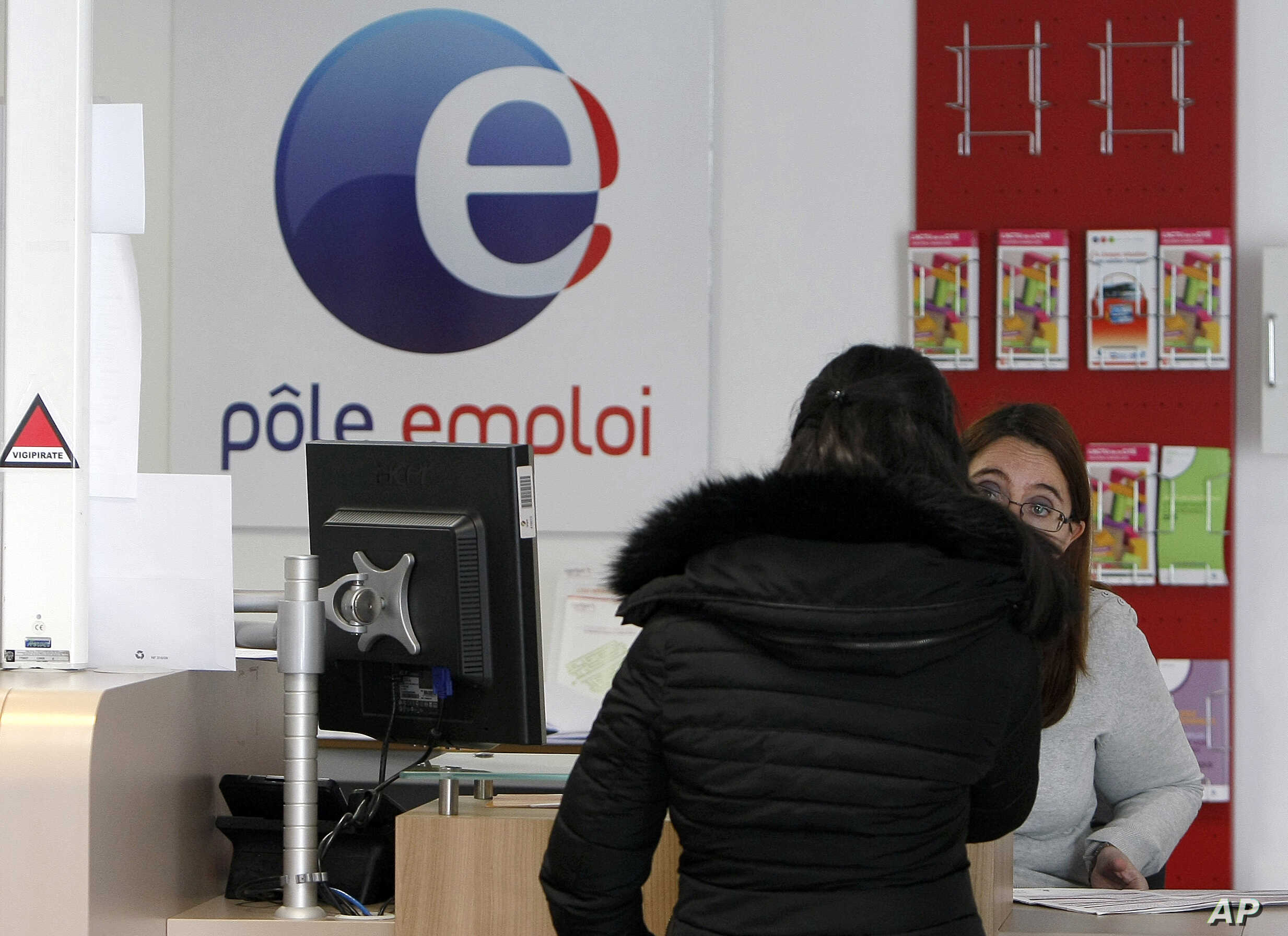 A job seeker speaks to a clerk at an Employment Center in Marseille, southern France, Feb. 24, 2015.  Record-high unemployment started dragging French President Francois Hollande's popularity down just a few months after his election in  2012.