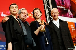 """Director, screenwriter, editor and producer Adina Pintilie and cast members pose with the Golden Bear award for best film, """"Touch Me Not,"""" at the news conference after the awards ceremony at the 68th Berlinale International Film Festival in Berlin, G"""